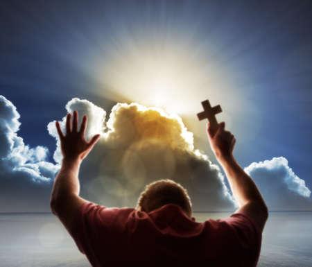 praise: Orar hombre levanta sus manos en oración y sostiene una cruz en el cielo con la puesta de sol celestial a través de un concepto celaje de religión, adoración, amor y espiritualidad
