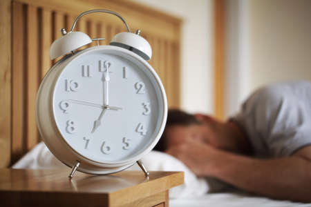 Man sleeping with alarm clock foreground concept for morning, time to wake up or fatigue photo