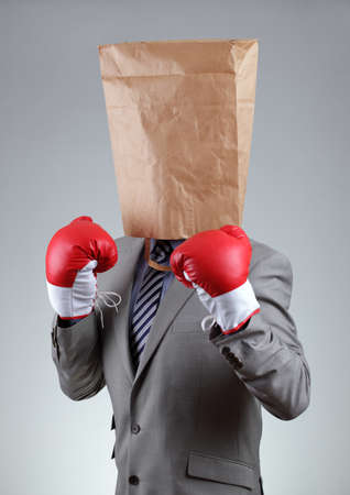 Businessman with paper bag on his head wearing boxing gloves concept for tough business, recruitment or anonymous bullying, copy space on bag photo