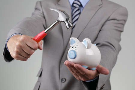 Businessman with hammer about to smash piggy bank to get at corporate savings photo
