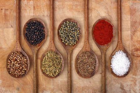 especias: Cucharas de madera llenas de hierbas aromáticas y especias en una tabla de cortar de madera