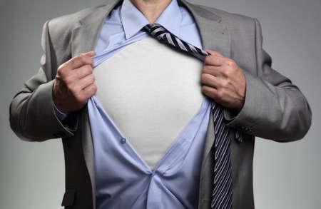 camisa: Hombre de negocios en actitud cl�sica que rasga su camisa abierta para revelar la camiseta con el pecho blanco para el mensaje Foto de archivo