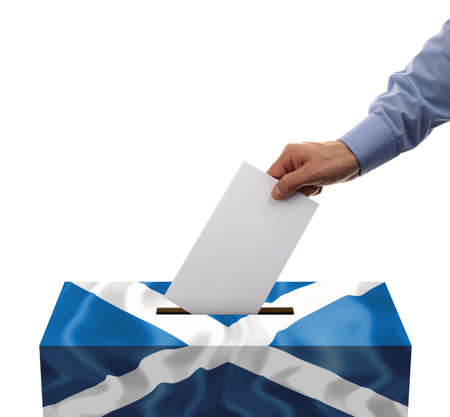 voter registration: Scottish independence referendum ballot box covered in scotlands flag with person casting vote on blank voting slip Stock Photo