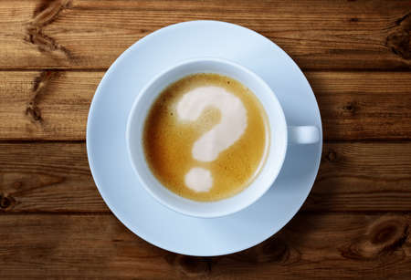 preguntando: Taza de café con el signo de interrogación en el concepto de la espuma para los problemas, la incertidumbre y hacer preguntas Foto de archivo