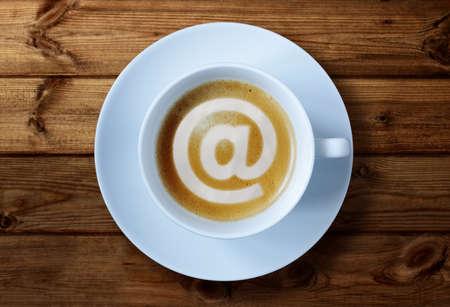cafe internet: 'At' s�mbolo en concepto de la taza de caf� de las redes sociales, e-mai, caf� internet o reuni�n de negocios Foto de archivo