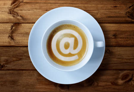 cafe internet: 'At' símbolo en concepto de la taza de café de las redes sociales, e-mai, café internet o reunión de negocios Foto de archivo