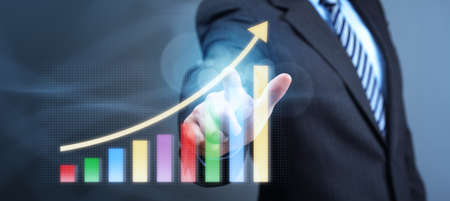 Businessman pointing to a growth chart showing business success photo