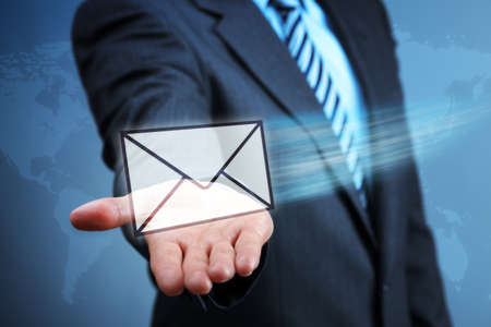 mail us: Businessman holding a virtual envelope concept for e-mail, global communications, mail or contact us