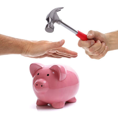 protecting your business: Hand with hammer about to smash piggy bank to get at savings being protected by another hand concept for protecting your assets, financial help and insurance