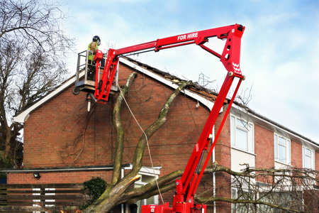 damaged roof: Tree surgeon working up cherry picker repairing storm damaged roof after an uprooted tree fell on top of a residential house Stock Photo