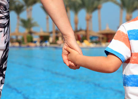 responsibilities: Mother and son holding hands on vacation looking at swimming pool concept for family vacations, child safety and single parent holiday Stock Photo