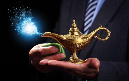 lampara magica: Empresario de la celebración y frotando un Aladdins concepto genio de la lámpara mágica para las aspiraciones de negocio, esperanza y deseos Foto de archivo