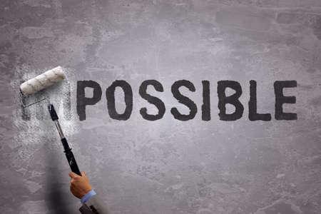 Veranderen van het woord onmogelijk om mogelijk door het schilderen op en wissen van een deel van het woord met een verfroller op een betonnen muur Stockfoto