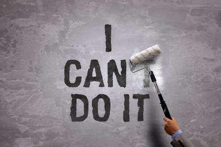 Cambiare la parola non può can dipingendo sopra e cancellare una parte di esso con un rullo di vernice su un muro di cemento nella frase posso farlo