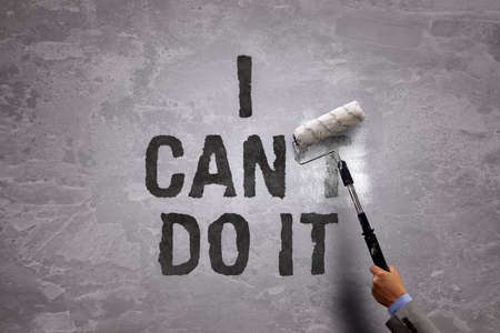 Changing the word cant to can by painting over and erasing part of it with a paint roller on a concrete wall in the phrase i can do it