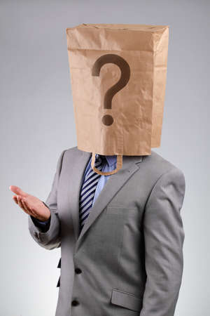 Anonymous businessman wearing a paper bag on his head with a question mark concept for  business recruitment, mystery shopper, failure or embarrassment photo