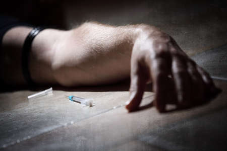 drug overdose: Drug addict with syringe lying down on the floor concept for self harm, shooting up and substance abuse