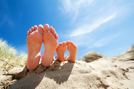 beach feet: Family feet relaxing and sunbathing on the beach concept for vacation and summer holiday