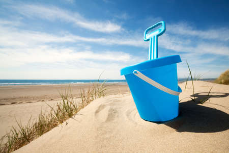 Childs bucket bucket and spade or sand pail and shovel at the beach on a sunny summer day photo