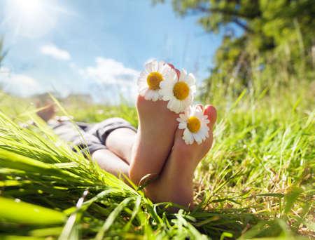 Criança com margarida entre os dedos deitada no prado relaxar no sol de verão