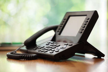 Business telephone with liquid crystal display on a desk in an office photo