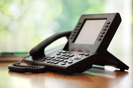 Zakelijke telefoon met LCD-scherm op een bureau in een kantoor