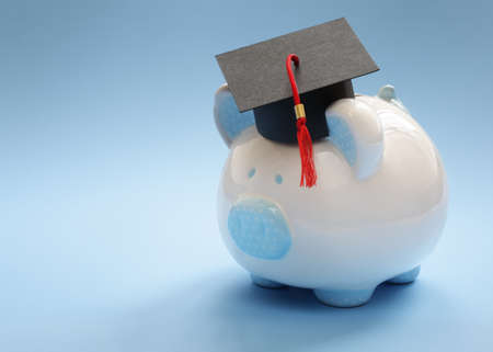 college fund savings: Piggy bank with a graduation mortar board cap concept for the cost of a college education Stock Photo