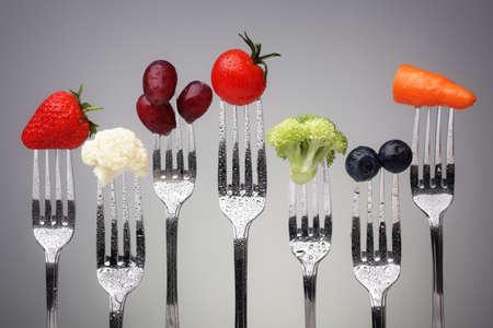 健康的な食事、ダイエット、抗酸化物質の灰色の背景概念に対する銀フォークの果物と野菜
