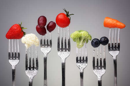 dieting: Groenten en fruit van zilveren vorken tegen een grijze achtergrond concept voor gezond eten, dieet en antioxidant