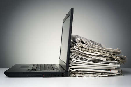 インターネットや電子オンライン ニュースのためのラップトップと新聞の概念