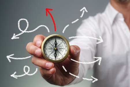 Businessman and compass showing direction concept for guidance, strategy and business orientation photo