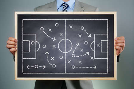 Business strategy businessman holding a blackboard planning team strategy on a chalk drawing of a soccer playing field photo