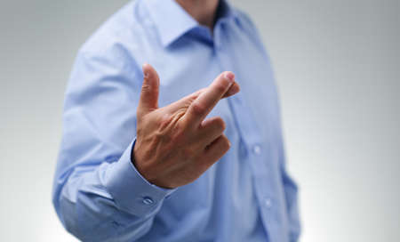 Businessman waiting with fingers crossed wishing for good luck photo