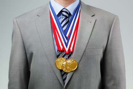 Gold medals hanging around a businessman neck concept for success and winning in business Stock Photo