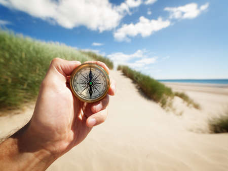 Hand holding a compass on the beach by sea concept for guidance, direction, and adventure Stok Fotoğraf - 29819222