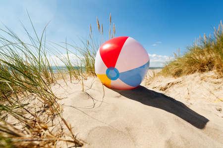 leuchtend: Beach-Ball ruht in Sanddüne Konzept für den Sommer Kindheit Urlaub, Familienurlaub und einen gesunden Lebensstil