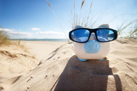 Holiday savings piggy bank on a beach vacation with sunglasses photo