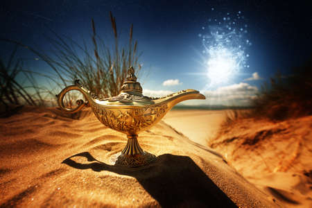 aladdin: Magic lamp in the desert from the story of Aladdin with Genie appearing in blue smoke concept for wishing, luck and magic