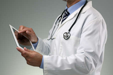 Docteur en utilisant tablette numérique sur fond gris