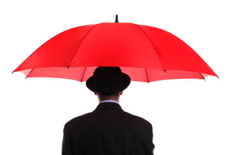 Businessman or insurance agent wearing a bowler hat holding a red umbrella  photo