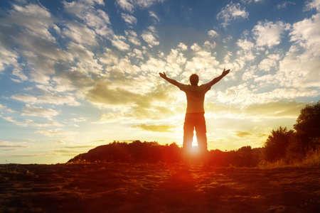 宗教、信仰、祈りと賛美の日没のコンセプトで育った手を持つ男のシルエット
