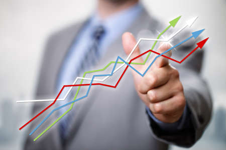 Businessman pointing to growth in a line graph showing business success photo