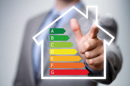 eficiencia energetica: El hombre de negocios que apunta a la eficiencia energética tabla de clasificación y casa icono concepto para el rendimiento, la eficiencia y la conservación del medio ambiente