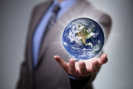 businessman carrying a globe: Businessman holding the glowing world in his hands  Earth image courtesy of Nasa at http:visibleearth.nasa.gov Stock Photo