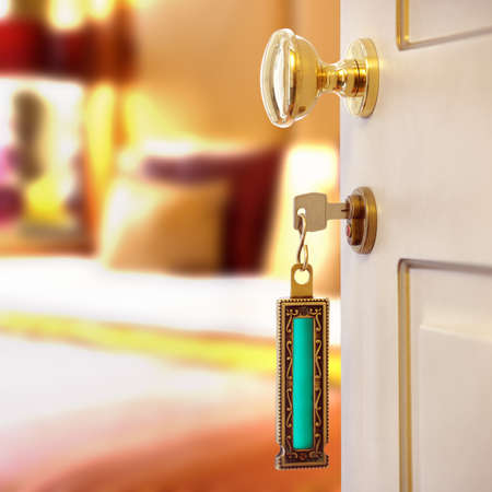 Hotel room or apartment doorway with key and keyring key fob in open door and bedroom in background photo