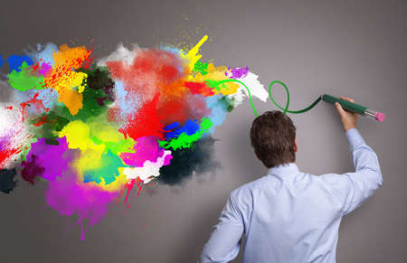 Zakenman schilderen abstract kleurrijk ontwerp op grijze achtergrond concept voor zakelijke creativiteit, verbeelding en inspiratie