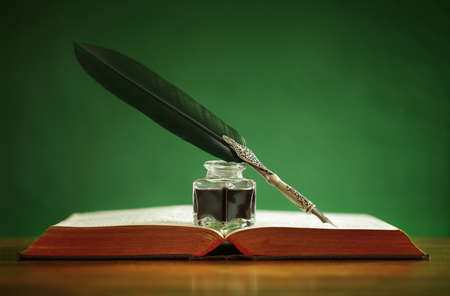 ink well: Quill pen and inkwell resting on an old book with green background concept for literature, writing, author and history