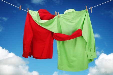 Wasserij opknoping op een waslijn concept voor de liefde en romace met twee shirts elkaar kijken omarmen op een blauwe hemel