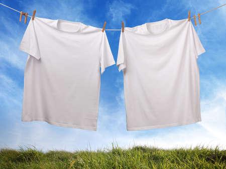 lavanderia: Camiseta blanca colgando de tendedero exterior con el frente blanco Foto de archivo
