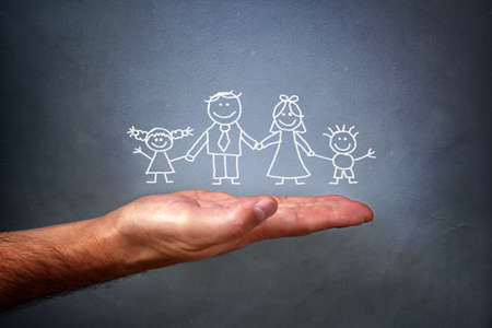 Childrens chalk drawing on a blackboard of a happy family with mom, dad, son and daughter holding hands being held in the palm of a mans hand photo